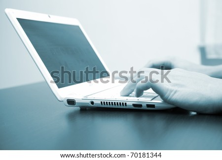 Closeup of male hands typing on a laptop - blue toned image - stock photo
