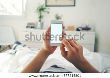 Closeup of male hands using smart phone with blank screen while lying in bed at morning - stock photo