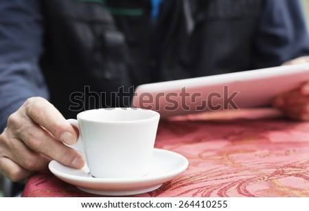 Closeup of male hands with with digital tablet surfing the net .The man sitting at the table in the cafe and drinking a coffee. - stock photo