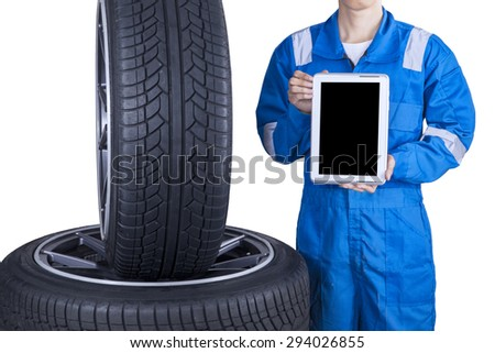 Closeup of male mechanic showing empty tablet screen near tires, isolated on white background - stock photo
