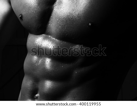 Closeup of male naked sporting muscular excellent belly with cool perfect abs pectoral and six-pack iron muscles black and white studio on dark background
