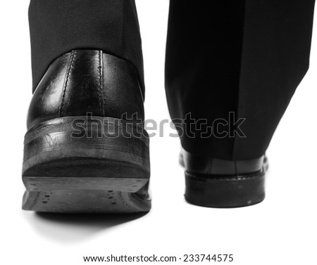 Closeup of male suit walking away in black worn shoes towards white - stock photo
