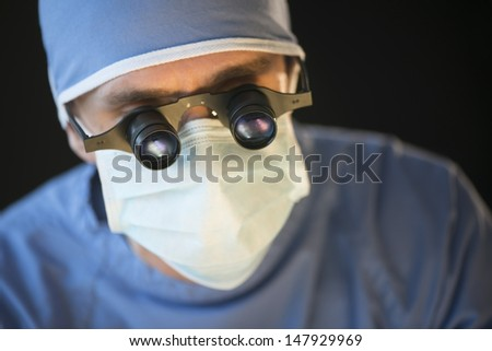 Closeup of male surgeon wearing mask and magnifying glasses against black background - stock photo