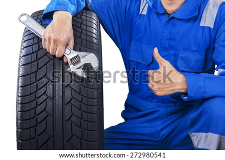 Closeup of males mechanic with a blue uniform holding a tire and wrench, showing thumb up - stock photo
