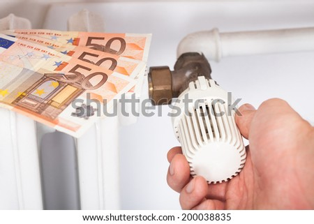 Closeup of man adjusting temperature on radiator thermostat by euro notes - stock photo