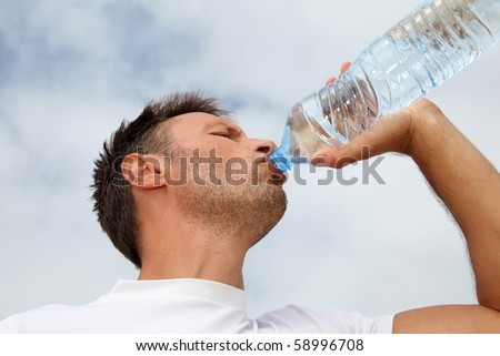 Closeup of man drinking water from bottle - stock photo