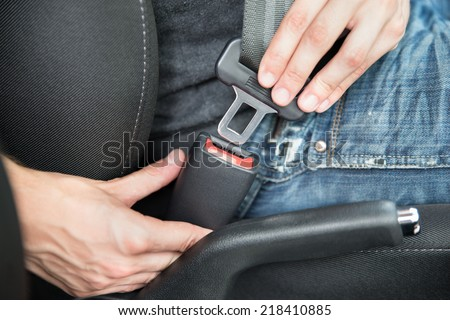 Closeup of man fastening seat belt in car - stock photo
