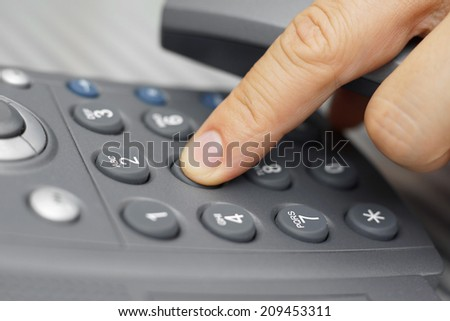 closeup of man finger is dialing a telephone number - stock photo