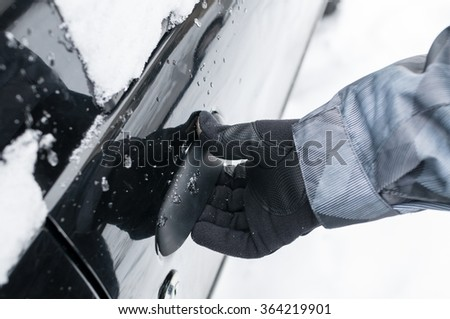 Closeup of man hand opening frozen car door in winter - stock photo