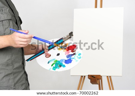 closeup of man holding brushes and palette, blank canvas on easel - stock photo