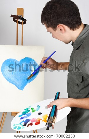 closeup of man holding brushes and palette, painting blue heart - stock photo