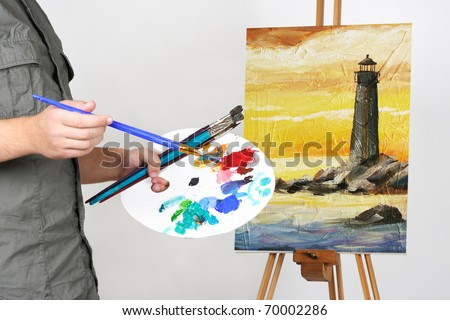 closeup of man holding brushes and palette, painting picture with sea landscape - stock photo