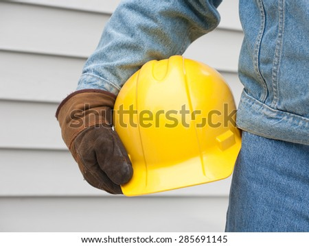 Closeup of man holding hardhat with house siding background. Man wearing denim and work gloves. - stock photo
