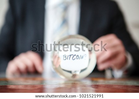 closeup of man holding paper with word Bitcoin in front of glass ball