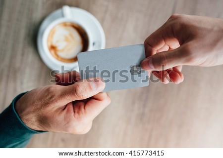 Closeup of man in cafe giving credit card to waiter
