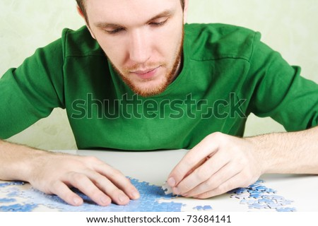 closeup of man in green shirt assembling blue puzzle pieces