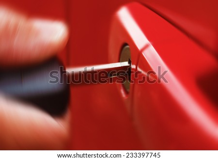 Closeup of man inserting key into car lock with radial blur - stock photo