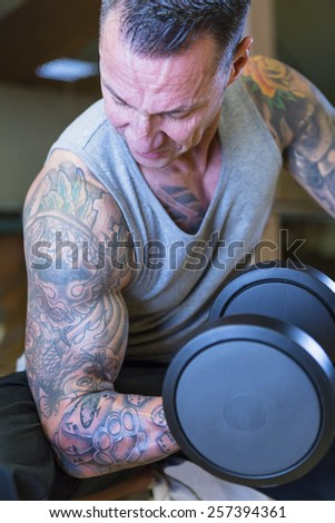 closeup of man making seated dumbbell concentration curl - bicep exercise - at the gym - finish exercise - focus on the man face - stock photo