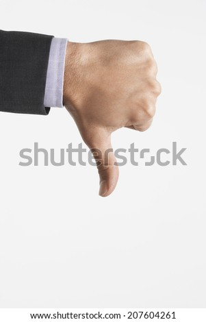 Closeup of man making thumbs down sign against white background - stock photo