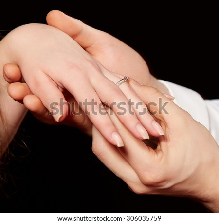 Closeup of man placing engagement ring in woman's finger against black background - stock photo