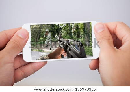 Closeup of man playing action game on smartphone - stock photo