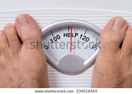 Closeup of man's feet on weight scale indicating Help - stock photo