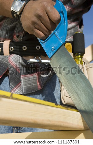 Closeup of man's hand sawing a plank of wood