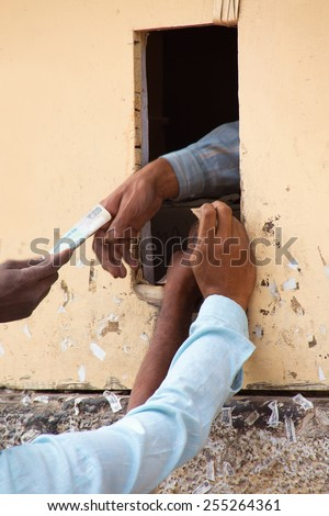 Closeup of man's hands buying alcohol through small window, New Delhi, India - stock photo