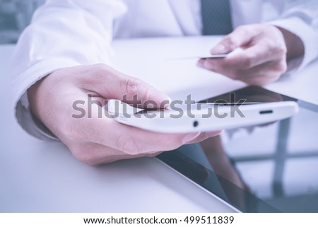Closeup of man's hands holding credit cards and using mobile phone. Concept for m-commerce, online shopping, m-banking, internet security.