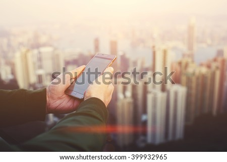 Closeup of man`s hands is holding cellphone with copy space screen for your advertising text message of promotional content. Male CEO is reading news in network via mobile phone during work break - stock photo