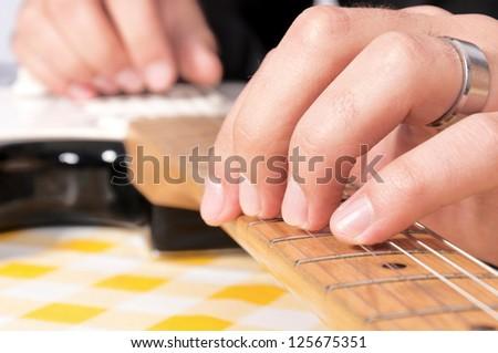 Closeup of man's hands playing bass guitar DOF focus on fingers - stock photo