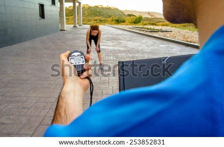 Closeup of man trainer hand using a chronometer to timing at tired athletic young woman in a hard training outdoors - stock photo