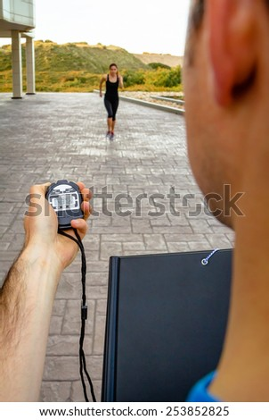 Closeup of man trainer hand using a chronometer to timing athletic young woman in a hard training outdoors - stock photo