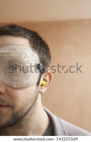 Closeup of man wearing protective eyegoggles and earplugs - stock photo