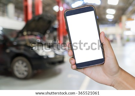 closeup of man with broken car and smart phone, Man hand holding mobile smart phone , tablet,cellphone over Blurred of car technician repairing the car in garage background.  - stock photo