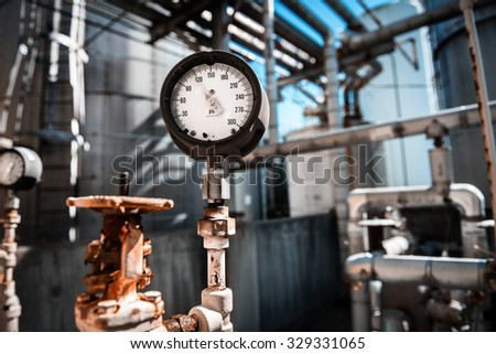 Closeup of manometer, measuring gas pressure. Pipes and valves at industrial plant.  - stock photo