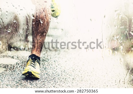 Closeup of mans foot touching the asphalt rainy weather, filter applied - stock photo