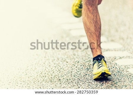 Closeup of mans foot touching the asphalt, warm filter applied - stock photo