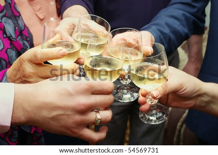 Closeup of many hands making toast with champagne with selective focus - stock photo