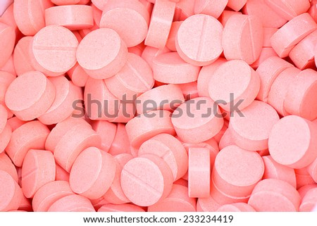 closeup of many pink pills for health care concept or background