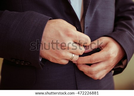 Closeup of married man's hands buttoning up black jacket