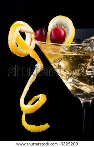 Closeup of martini glass with lemon and cranberry splash cocktail over black background - stock photo