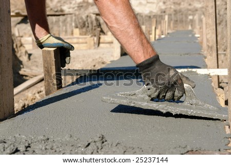 Closeup of mason's hand spreading concrete mix with trowel in foundation shuttering - stock photo
