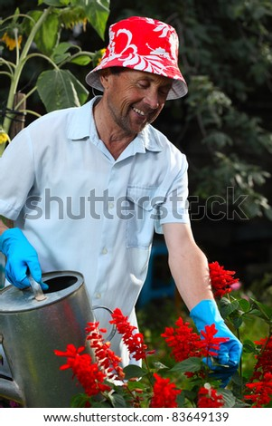 Closeup of mature caucasian smiling man watering her garden with a lot of flowers - stock photo