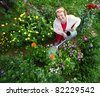 Closeup of mature caucasian smiling woman watering her garden with a lot of flowers - stock photo