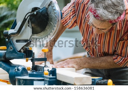 Closeup of mature man sawing lumber with sliding compound miter saw outdoors.  - stock photo