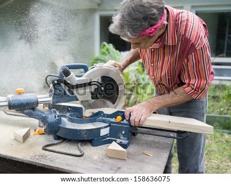 Closeup of mature man sawing lumber with sliding compound miter saw outdoors, sawdust flying around - stock photo