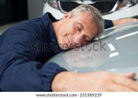 Closeup Of Mature Mechanic With Eyes Closed Lying On Car Bonnet Hugging - stock photo