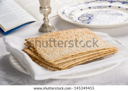 Closeup of Matzah on Plate which is the unleaven bread served at Jewish Passover dinners  with Kiddush cup and Sedar plate as well as Haddah