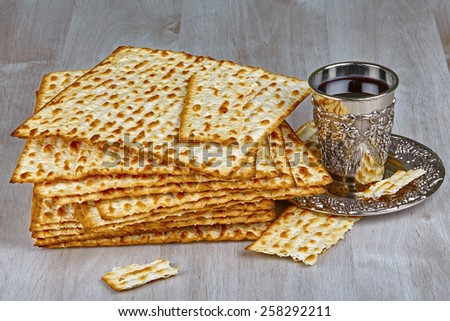 Closeup of Matzah with kiddush cup of wine on wooden table  - stock photo